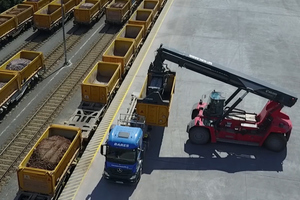 """<div class=""""bildtext_en"""">Loading a yellow intermodal container with a reach stacker</div>"""