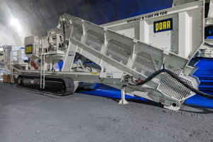 A crawler-mounted jaw crusher GIPOBAC B 1385 PB-FDR with plate-conveyor feed and separate pre-screener