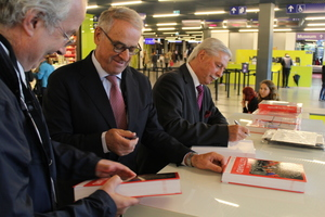 """<div class=""""bildtext_en"""">Adolf Ogi (middle) and STS president Luzi Gruber (right) sign copies of """"Tunnelling the Gotthard"""" for guests 