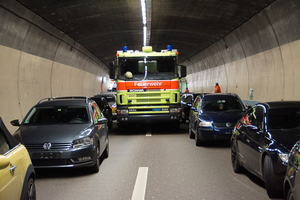 "<div class=""bildtext_en"">The Dietikon fire service in action in the 3.2 km long Gubrist Tunnel in June 2012 (on the left): the firefighting vehicle cannot advance any further in the two-lane road tunnel. View turned 180 ° (on the right): extinguishing operations have already started in parallel, with the cross-passages set up at 265 m gaps providing good working conditions as far as the problem of penetration depth is concerned</div>"