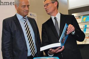 """VDV president Jürgen Fenske (r.) hands over the new """"Blue Book"""" to Federal Minister Dr. Peter Ramsauer (l.)."""
