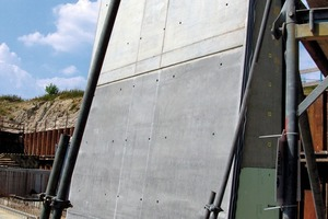 A completed section of the wing wall which tapers at the side facing the water. The upper lighter concrete part is the exposed concrete section.