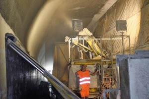 Shotcreting of the fireproof mortar on to the concrete roof of the Cassanawald Tunnel, using spraying robots mounted on rail flatcars
